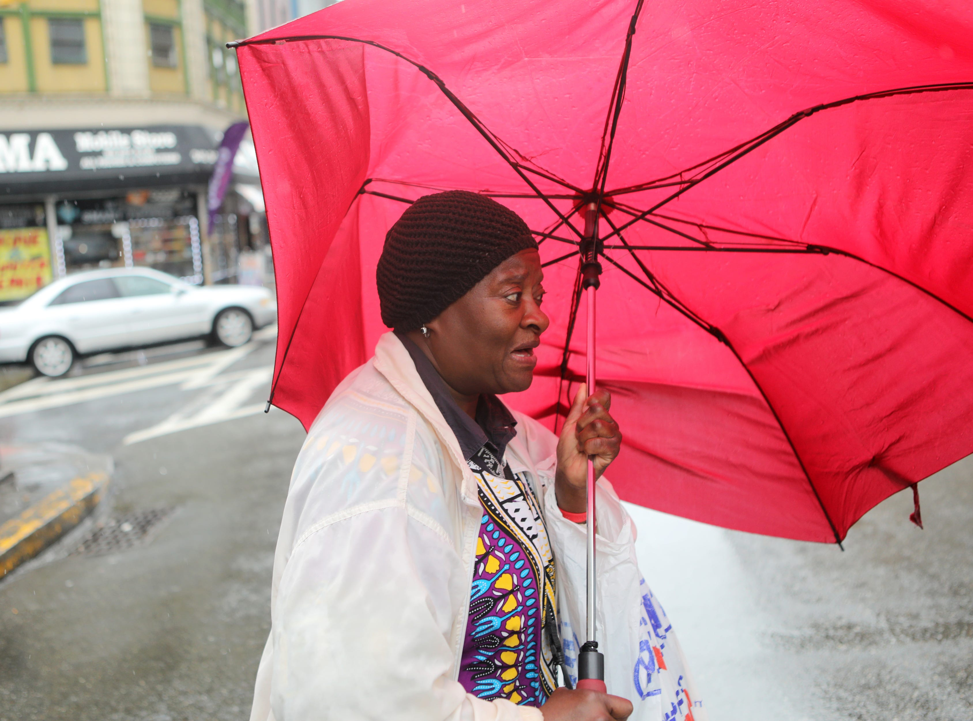 Mae Gregg, of Paterson, reacts as the power of the wind bends her umbrella, while she crosses Main St.  Monday, April, 15, 2019
