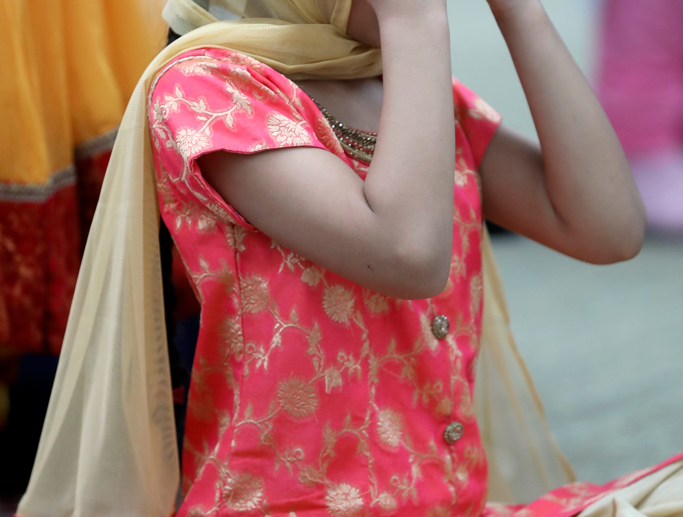 A girl places a head covering on at Guru Nanak Mission. Sunday, April, 14, 2019