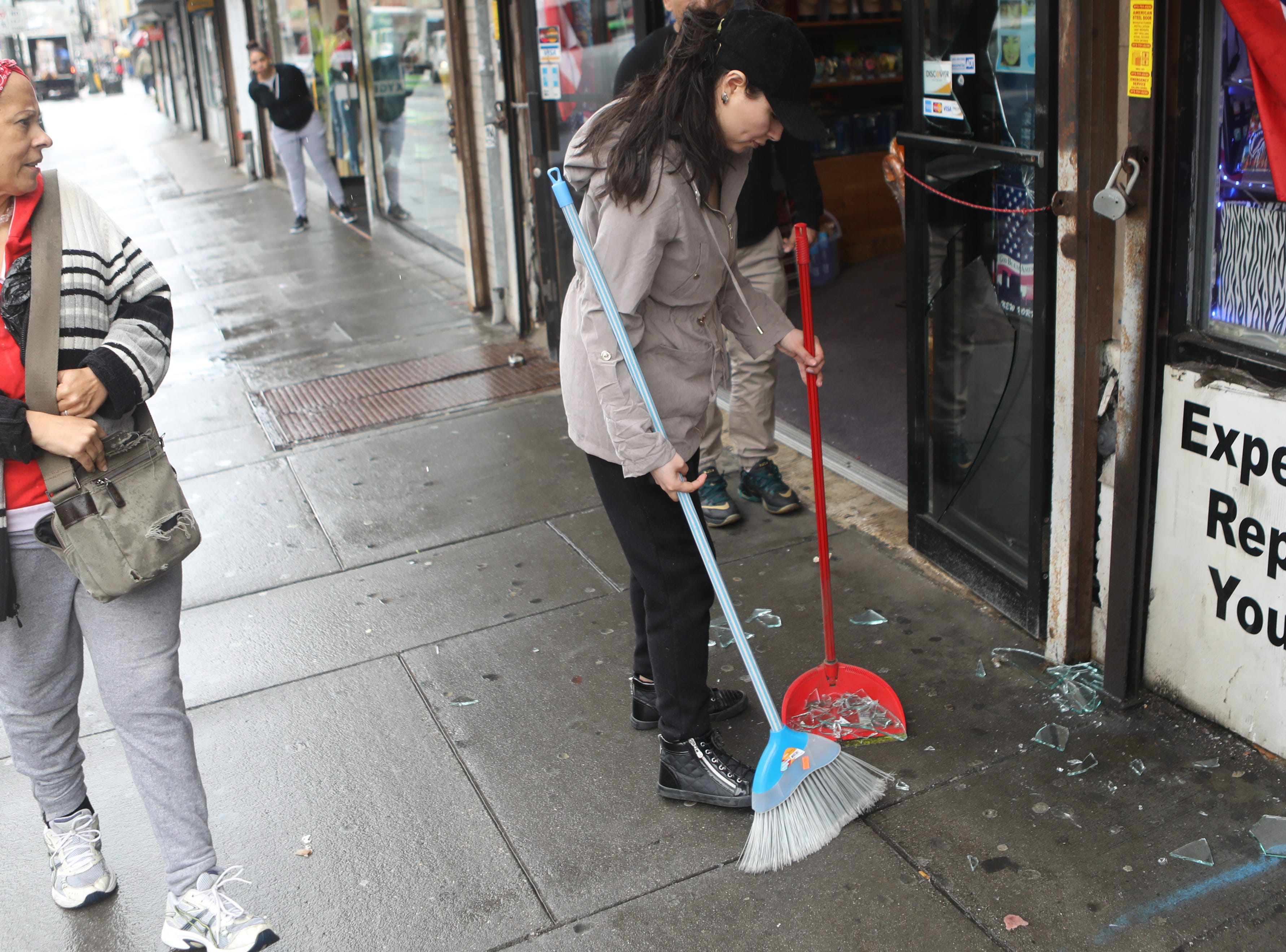 A woman sweeps glass off the sidewalk after the power of the wind blew a glass door open at City Fashion, on Main St. in Paterson. Monday, April, 15, 2019