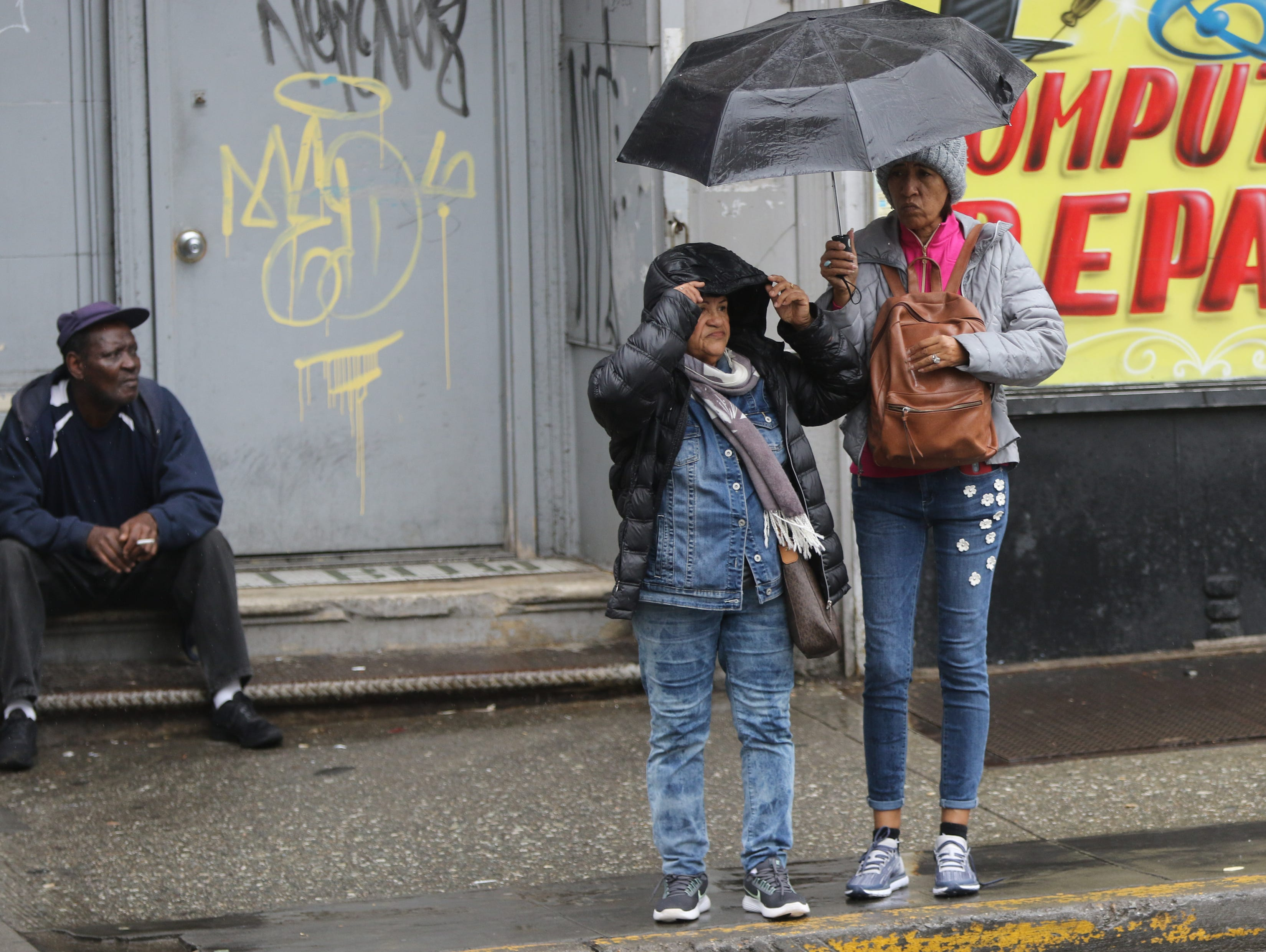 People are shown on the corner of Market and Main St. in Paterson, during a rain storm, Monday, April, 15, 2019.