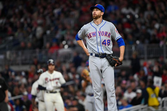 New York Mets' Jacob deGrom (48) takes a deep breath after walking Atlanta Braves Freddie Freeman, left, during the third inning of a baseball game Sunday, April 14, 2019, in Atlanta.