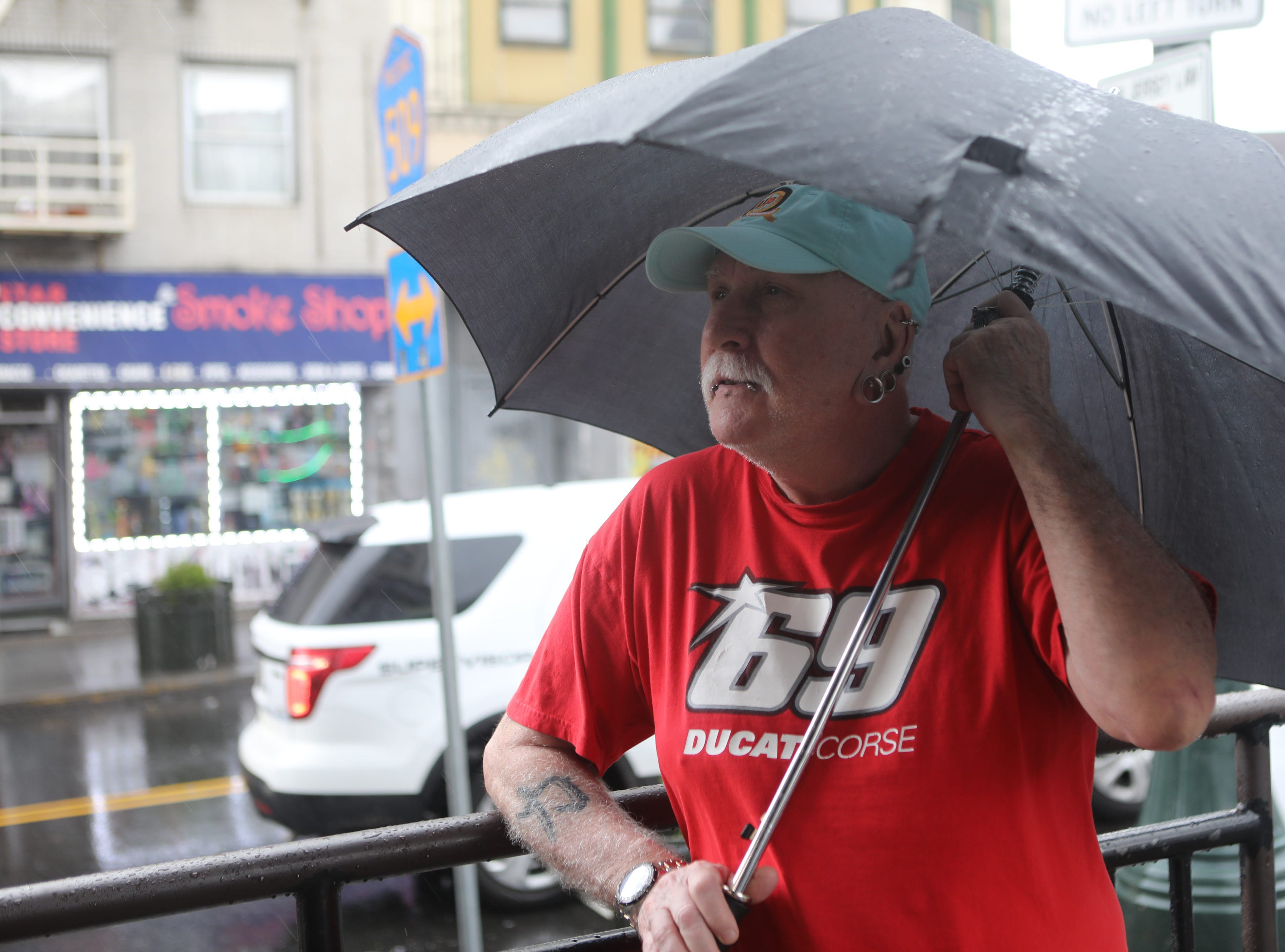 A man stands by the corner of Main and Market St. in Paterson as rain falls and the wind begins to increase. Monday, April, 15, 2019