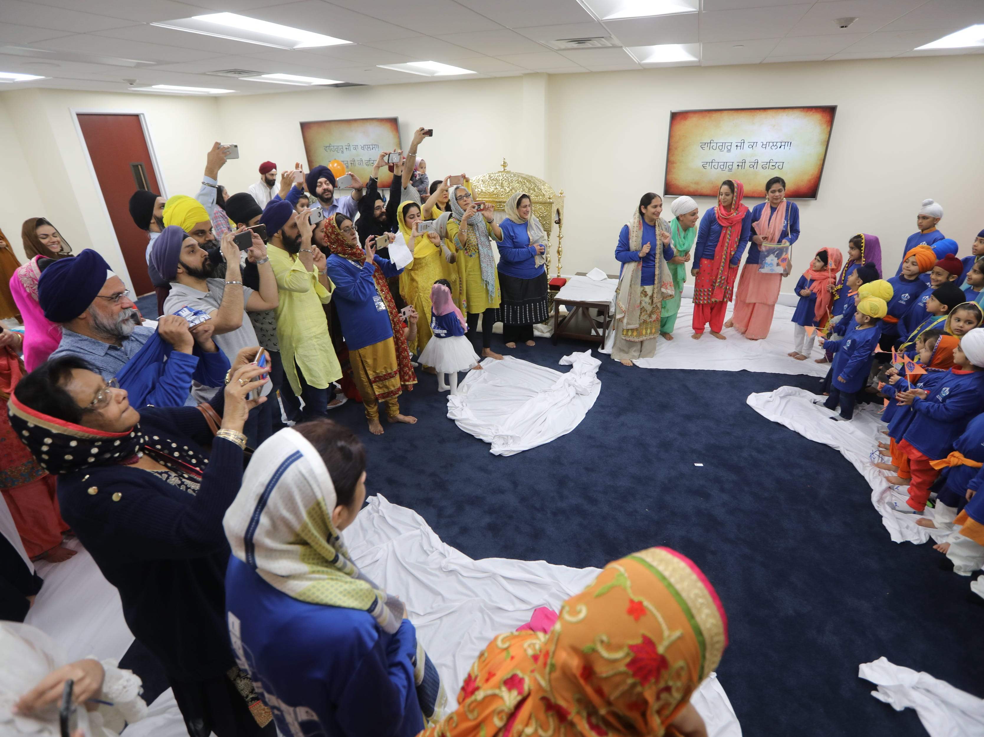 Parents and faculty members of the Guru Nanak Mission's Sikh Academy for Gurmat Education (SAGE), take pictures of students in Oakland. Sunday, April, 14, 2019