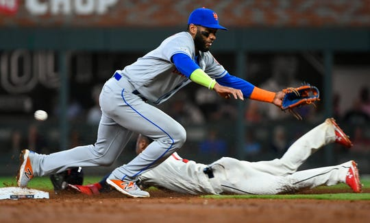 Atlanta Braves' Ozzie Albies steals second base as New York Mets shortstop Amed Rosario misses a wild throw by catcher Wilson Ramos during the third inning of a baseball game Sunday, April 14, 2019, in Atlanta. Albies advanced to third base and Ramos was charged with an error.