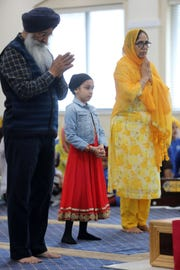Sharangit Singh, Kudrhe Kaur 5 and her grandmother, Surjid Kaur, all of Ramsey, pray in the main hall. Sunday, April, 14, 2019