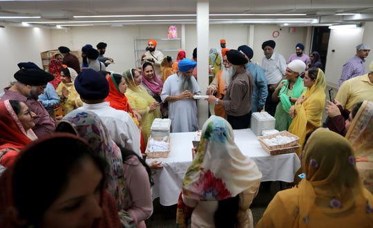 People line up to feed, Priest Kirtan Singh (blue turban)   his birthday cake.  Sunday, April, 14, 2019