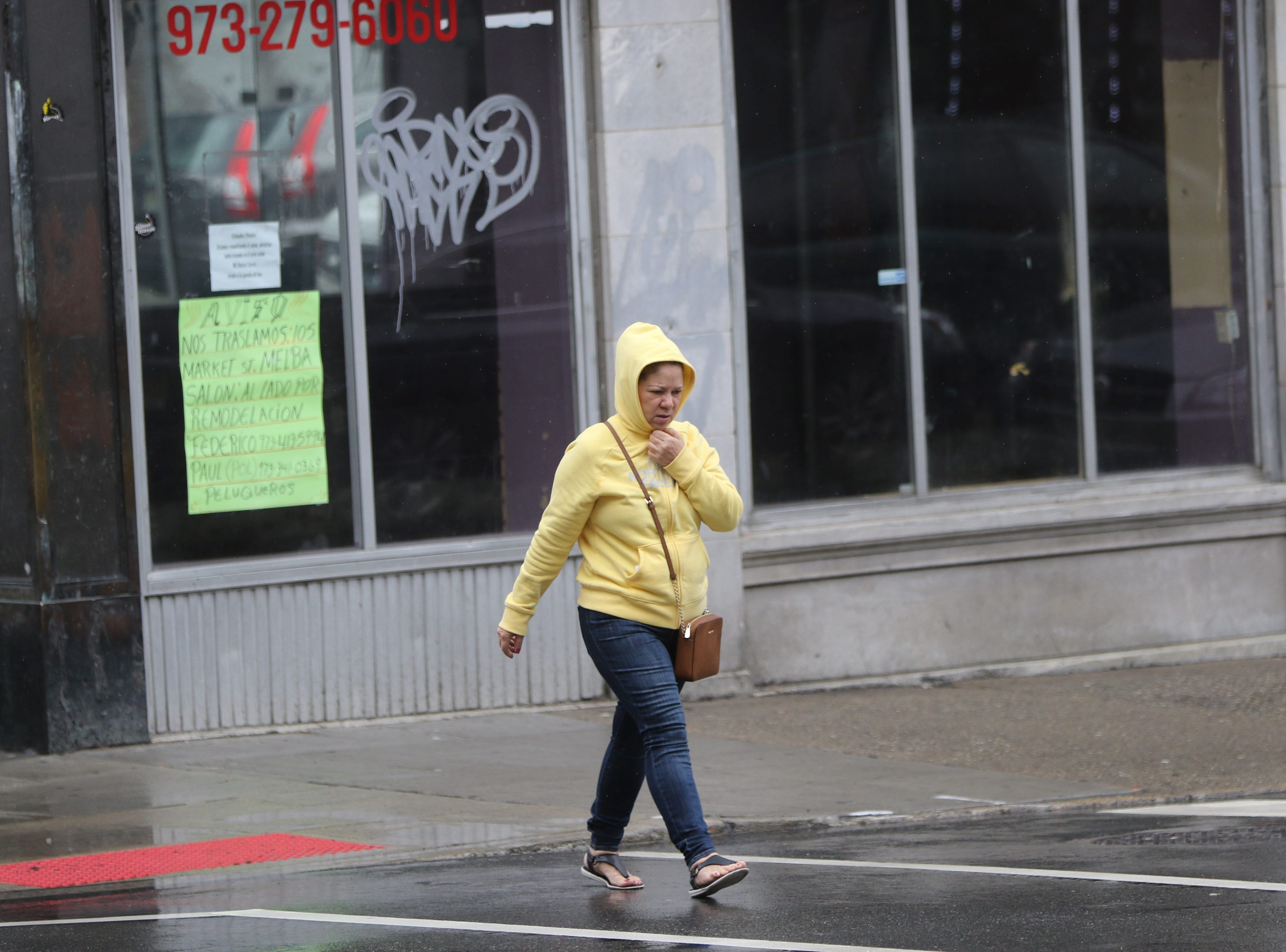 A woman tries to stay dry as she walks in Paterson.  Monday, April, 15, 2019