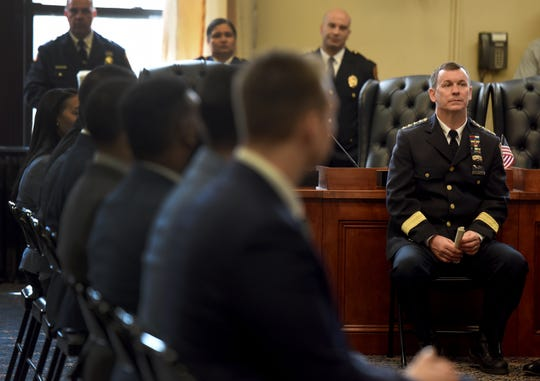 Paterson Chief of Police Troy Oswald, on right, attends a swearing-in ceremony for eight new Paterson police officers, seated on left, at Paterson City Hall on Monday, April 14, 2019.