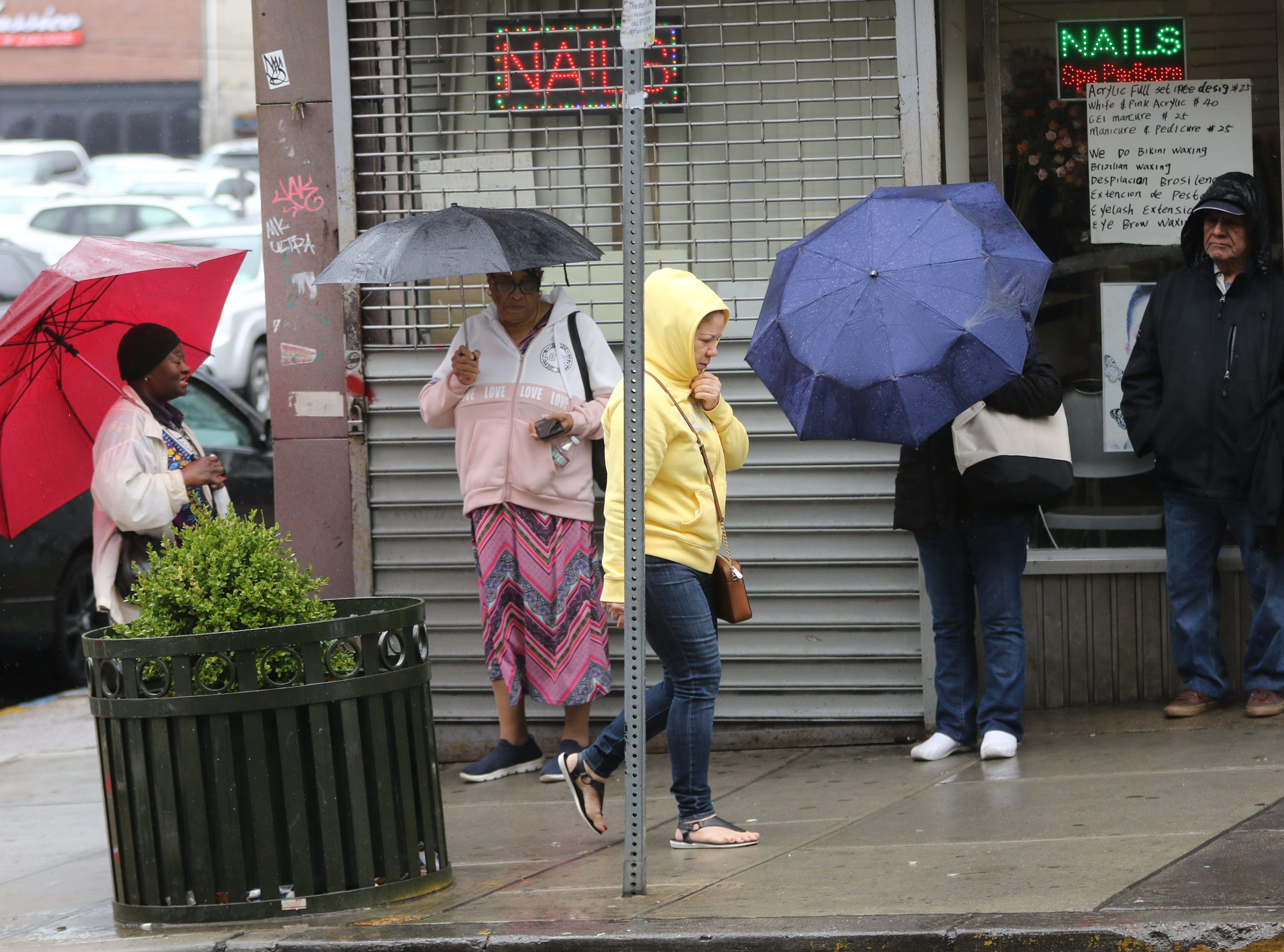 A woman tries to stay dry as she walks past others with umbrellas, on Market St. in Paterson.  Monday, April, 15, 2019