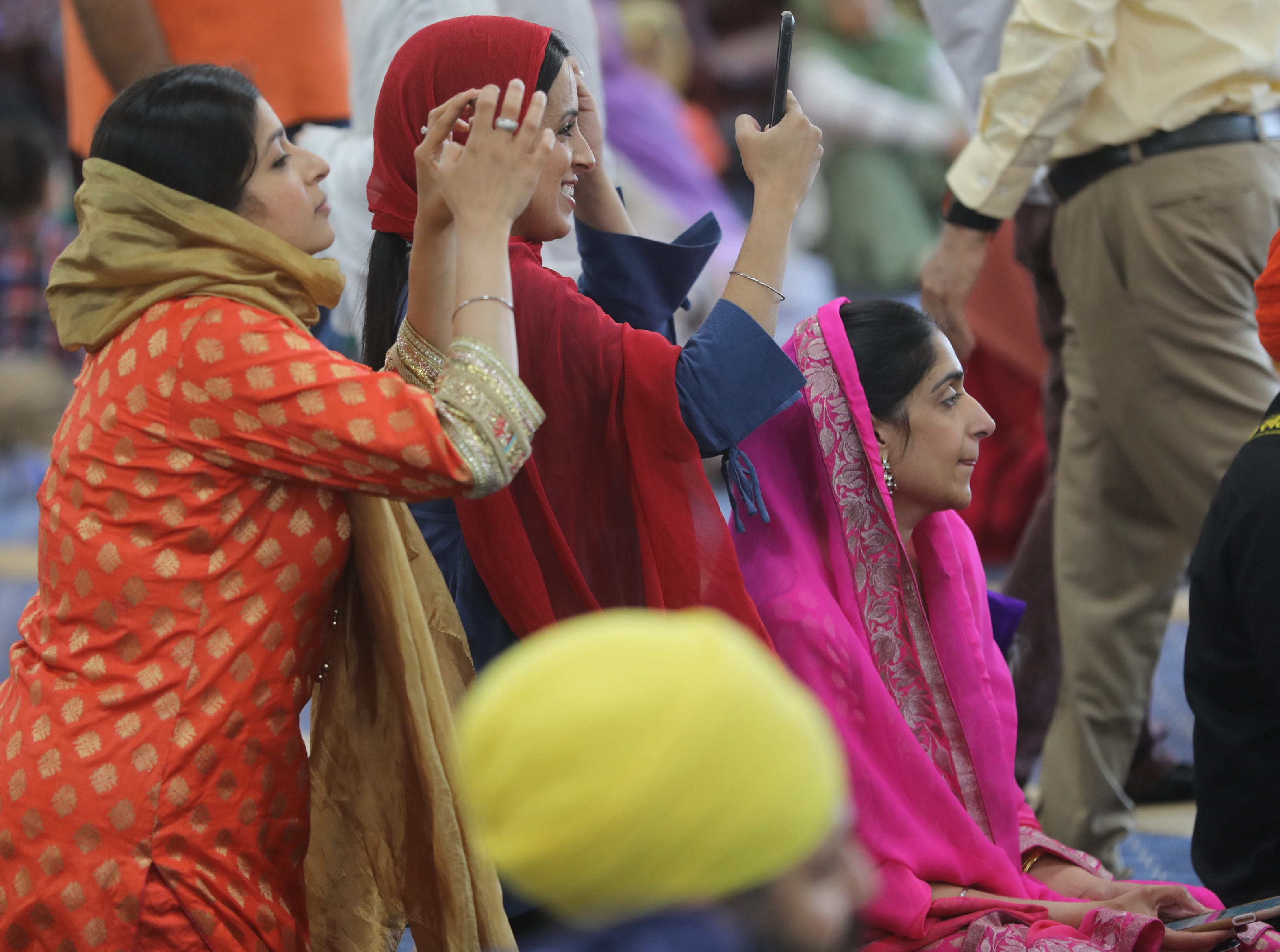 Parents of Guru Nanak Mission's Sikh Academy for Gurmat Education (SAGE) students, take pictures of them as they play instruments and sing in the main hall. Sunday, April, 14, 2019