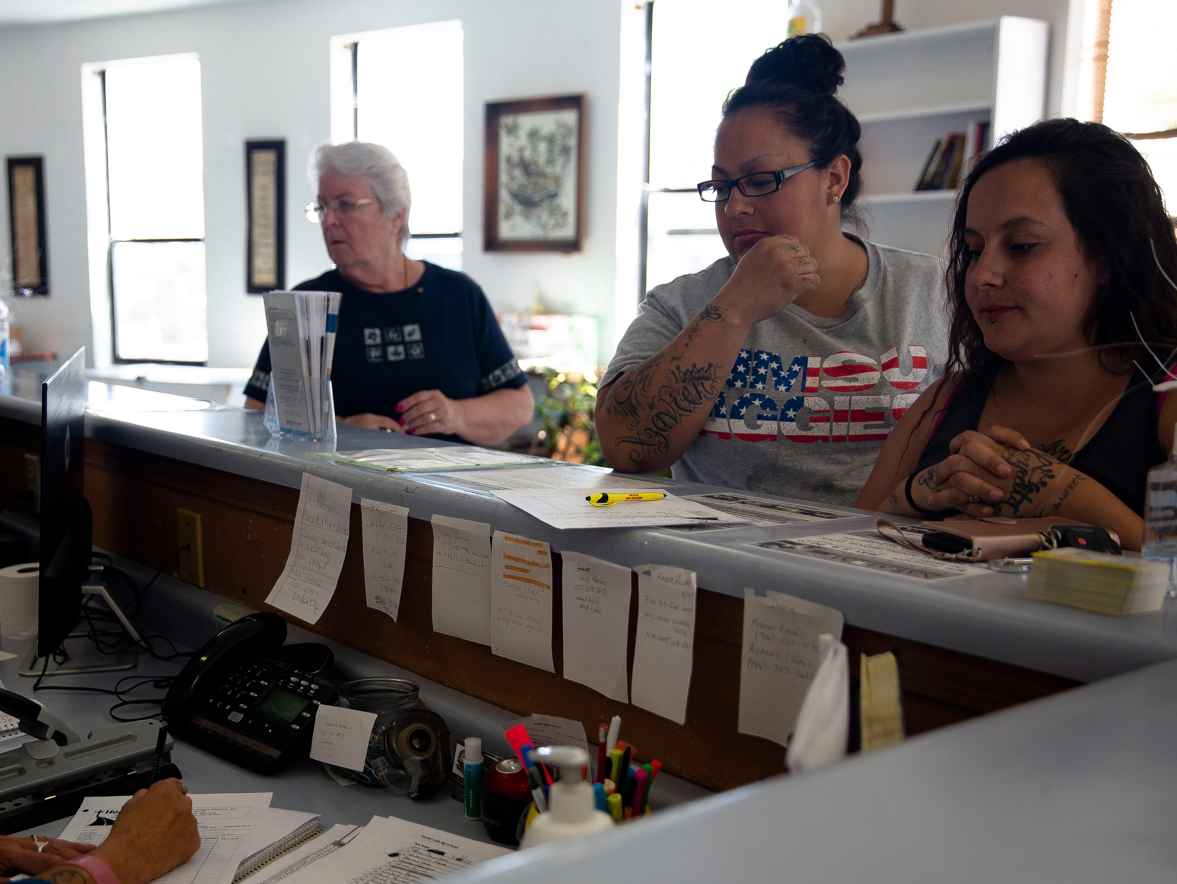 Las Cruces Gospel Rescue Mission worker Bob Reed talks with Sandra Beltran, background, who donated items for migrants Monday April 15, 2019, while shelter worker Chris Ostic, foreground, signs up volunteers Karen Escobedo, center, and Suzanne Lucero.