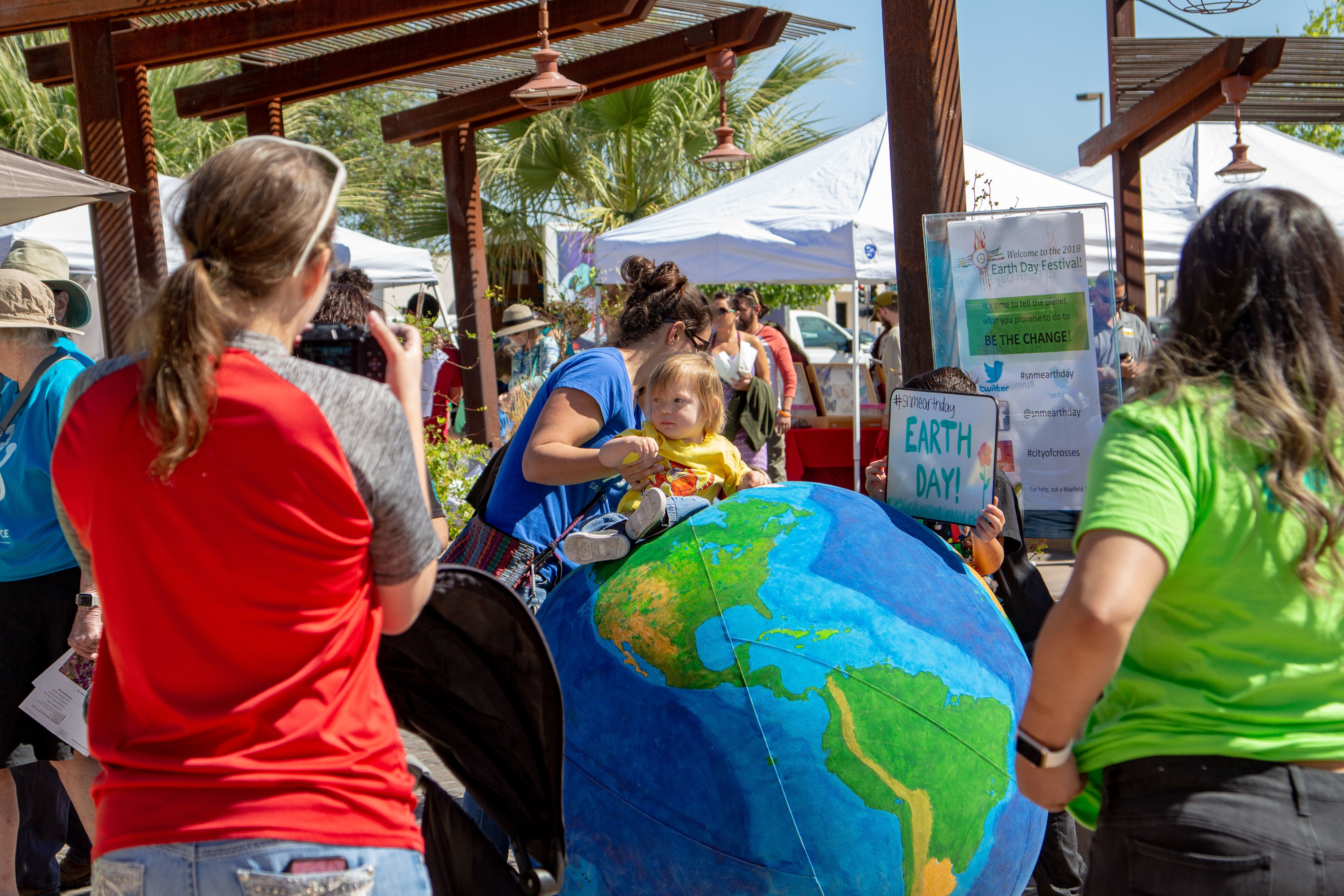 People take photos with the large inflatable Earth at the Earth Day celebration on April 21, 2018 at the Plaza de Las Cruces.