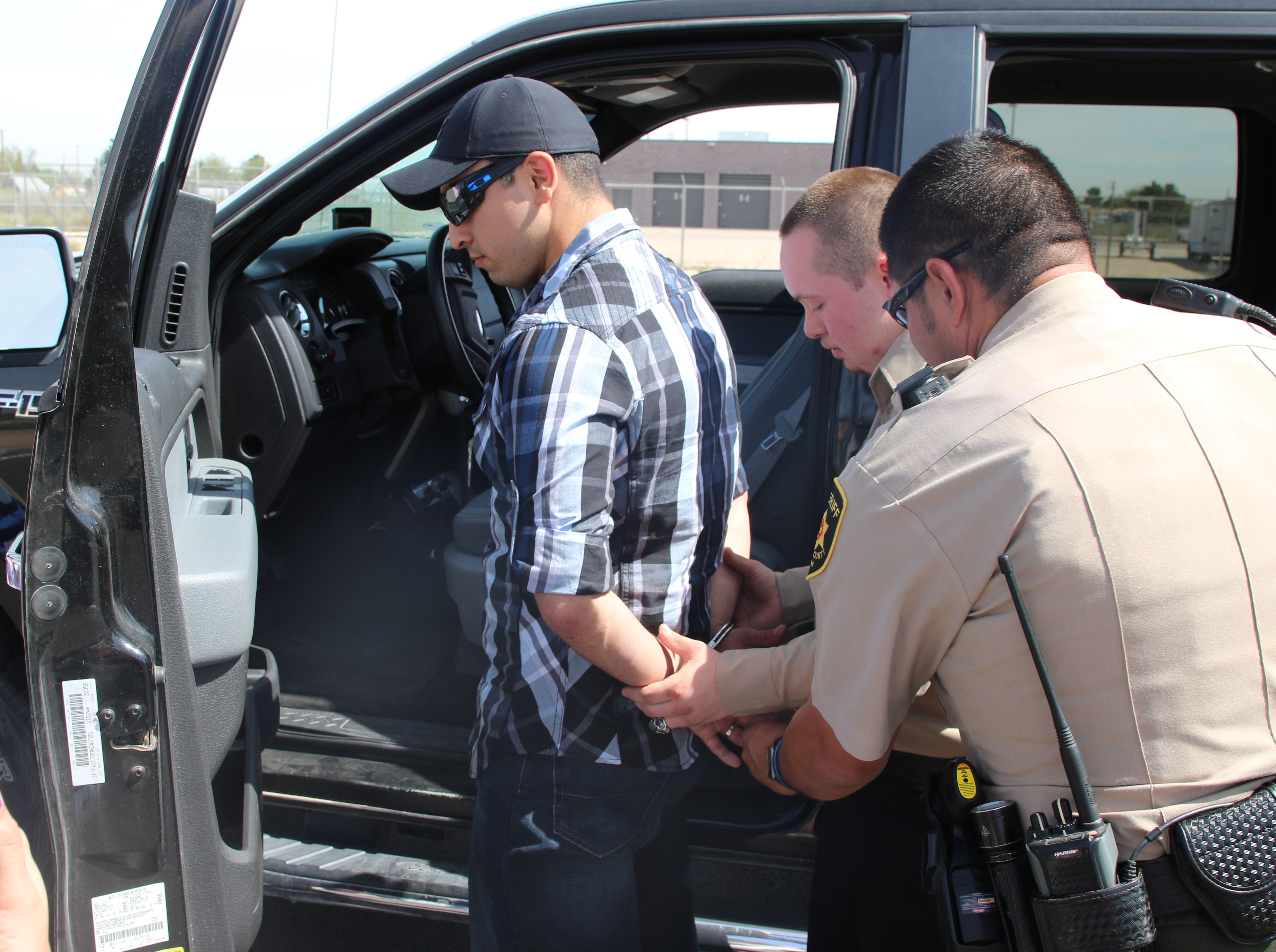 (From left)-Eddy County Sheriff's deputy Alexander Duchene is arrested by honorary sheriff's deputy Roman Leos and Adrian Rodriguez April 15. Leos' received a special birthday present from Eddy County Sheriff Mark Cage.