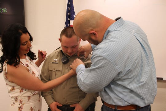 Yvette Leos watches as her husband Pecos Valley Drug Task Force commander Lennon Leos places a badge on Roman Leos. Eddy County Sheriff Mark Cage made Roman an honorary deputy during a birthday ceremony April 15.