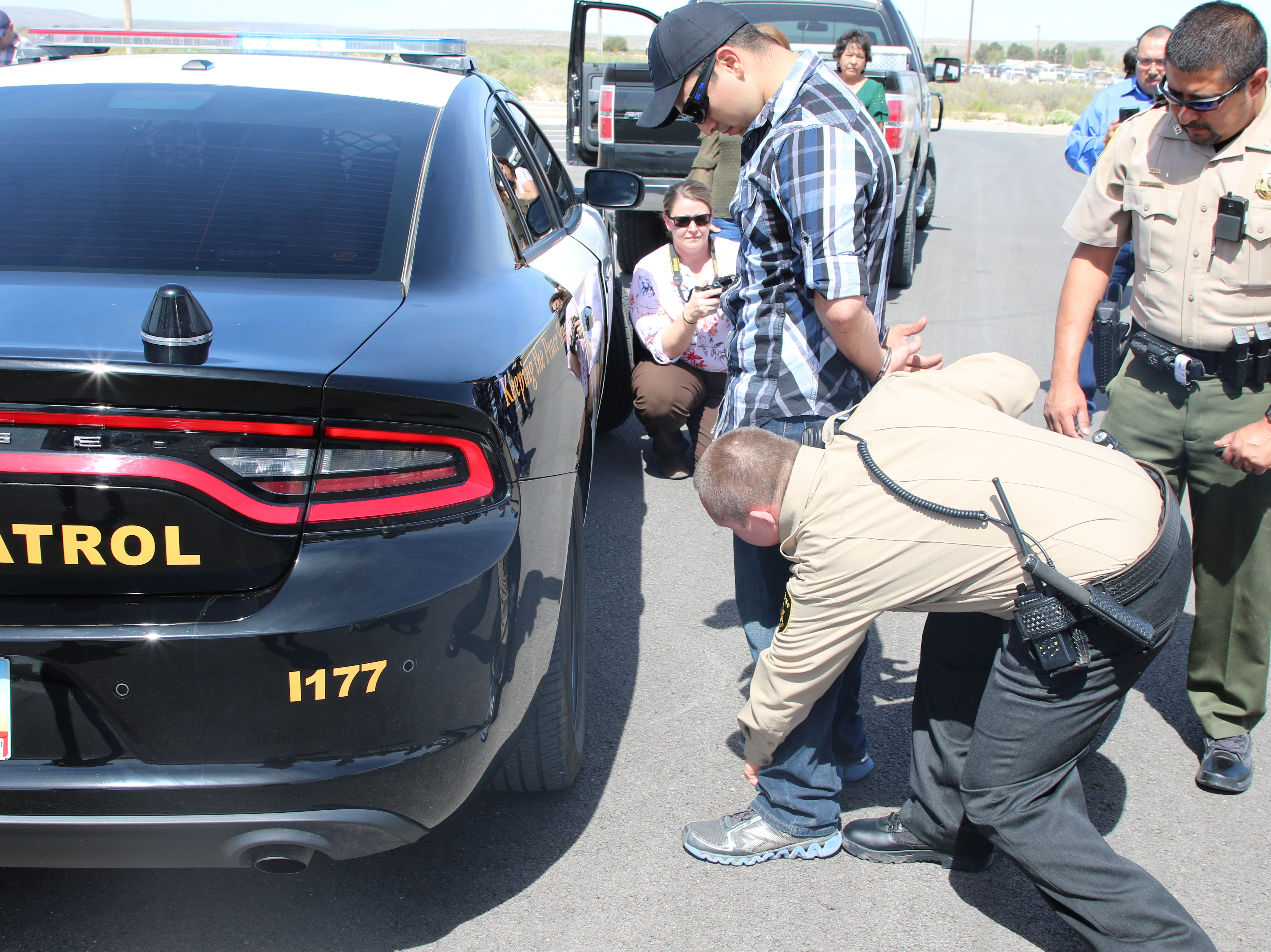 Honorary Eddy County Sheriff's deputy Roman Leos arrests Alexander Duchene with deputy Adrian Rodriguez looking on  April 15 at the Eddy County Sheriff's Office complex in Carlsbad. Leos received a birthday present from Eddy County Sheriff Mark Cage.