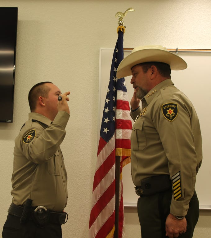Eddy County Sheriff Mark Cage swears in Roman Leos as an honorary deputy sheriff April 15.