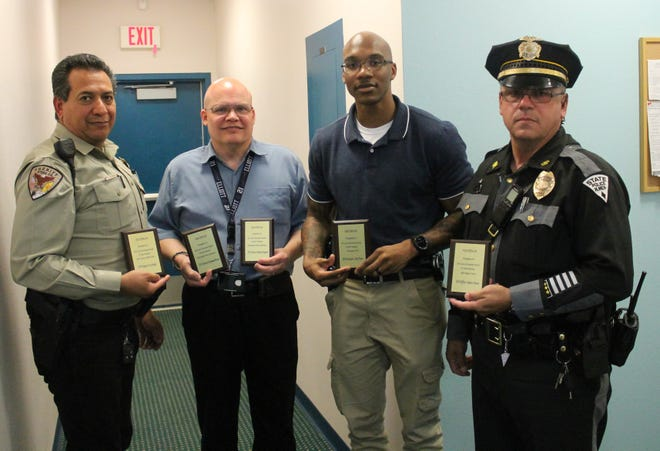 From left: Otero County Sheriff's Deputy Larry Roybal, CYFD County Office Manager for both Lincoln and Otero counties Larry Wisecup holds the plaques for the two APD officers Raymond Brown and Anthony Ferguson who could not attaend, Holloman Security Forces Investigator LaVon Thomas and New Mexico State Police Officer Andrew Hoover were honored at the fifth annual CYFD Law Enforcement appreciation luncheon.