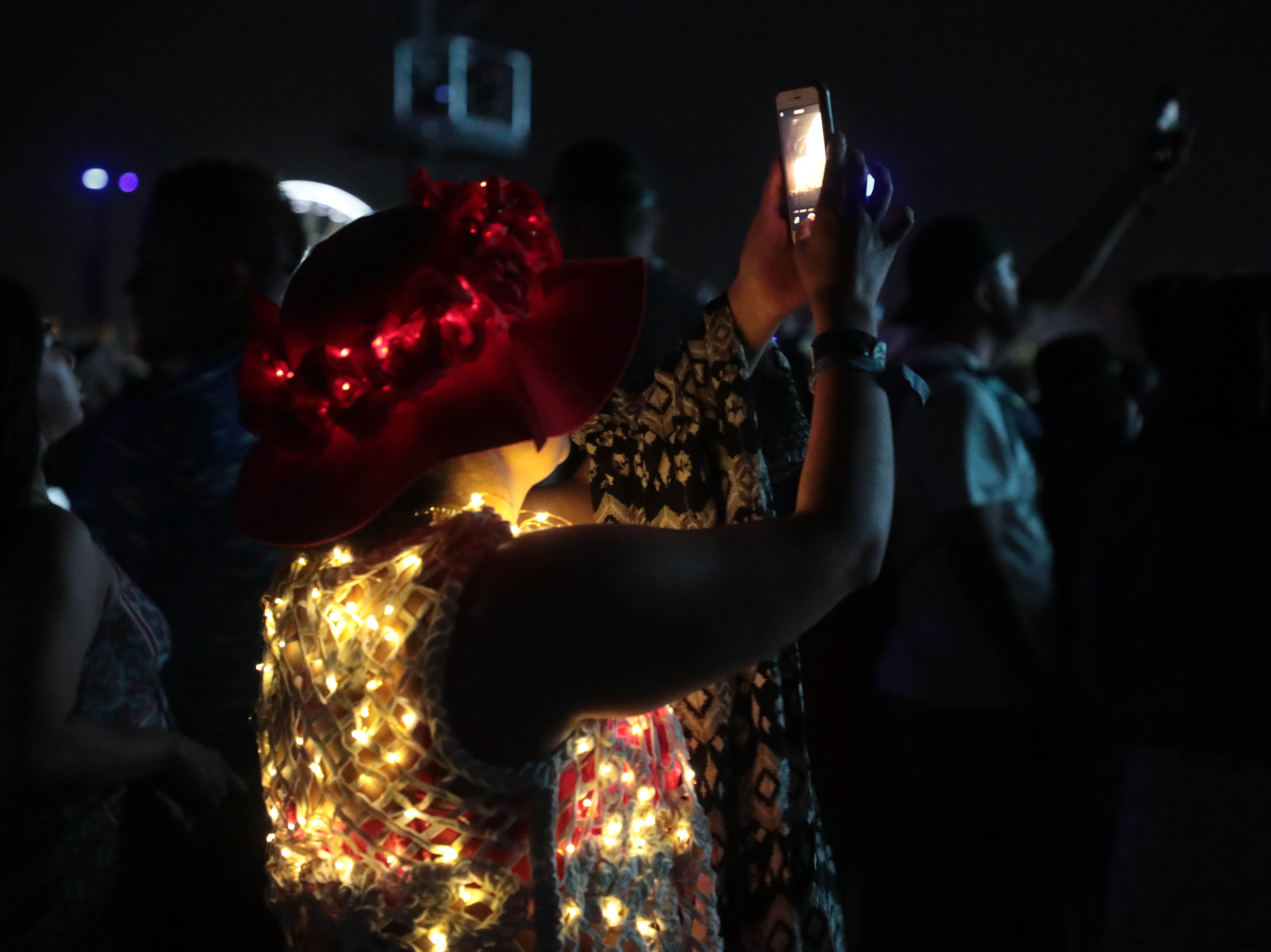 A woman takes a photo as Khalid performs at the Coachella Valley Music and Arts Festival on Sunday, April 14, 2019 in Indio, Calif.
