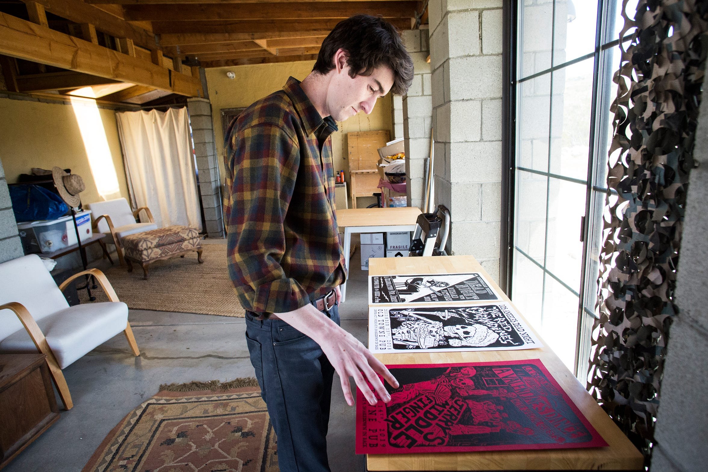 """Rudy Jansen, a """"deadhead"""" is photographed at his home in Morongo Valley in April of 2019. In this photo he looks at some of his drawings he has made of the Grateful Dead imagery."""