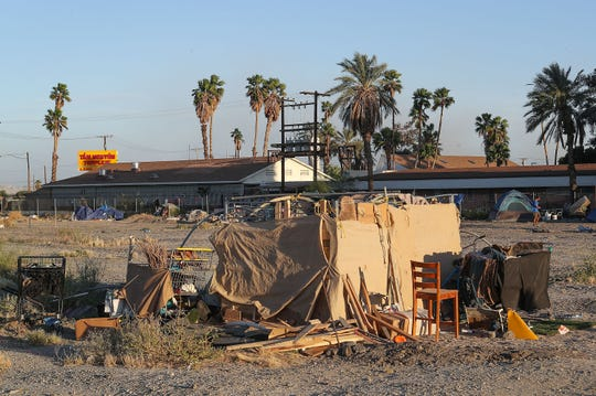 People experiencing homelessness have built makeshift camps where they are living in a large vacant lot near the intersection of Highway 111 and Van Buren St. in Indio, April 9, 2019.