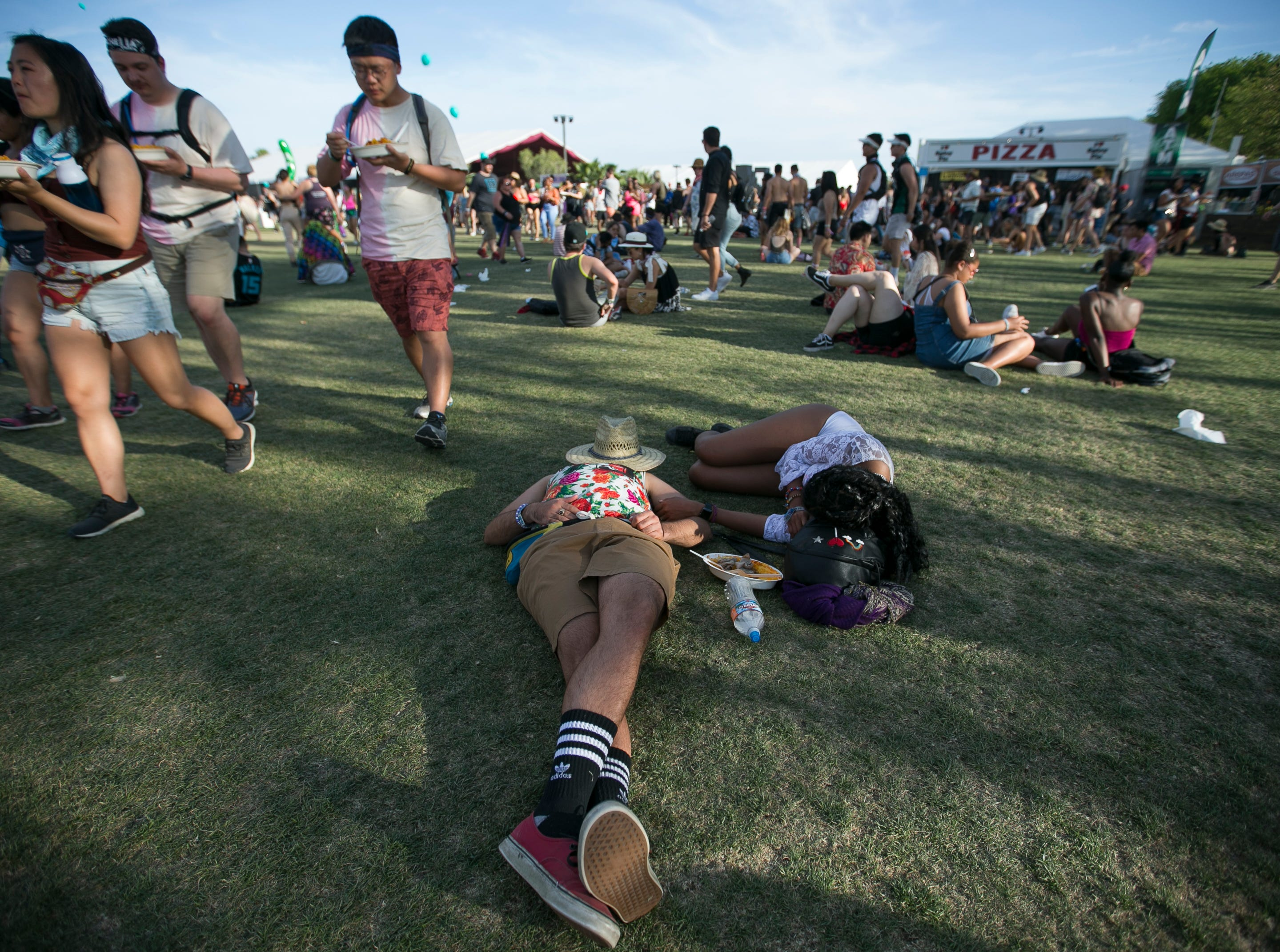 Festival goers lay in the grass at the Coachella Valley Music and Arts Festival in Indio, Calif., on Sunday, April 14, 2019.