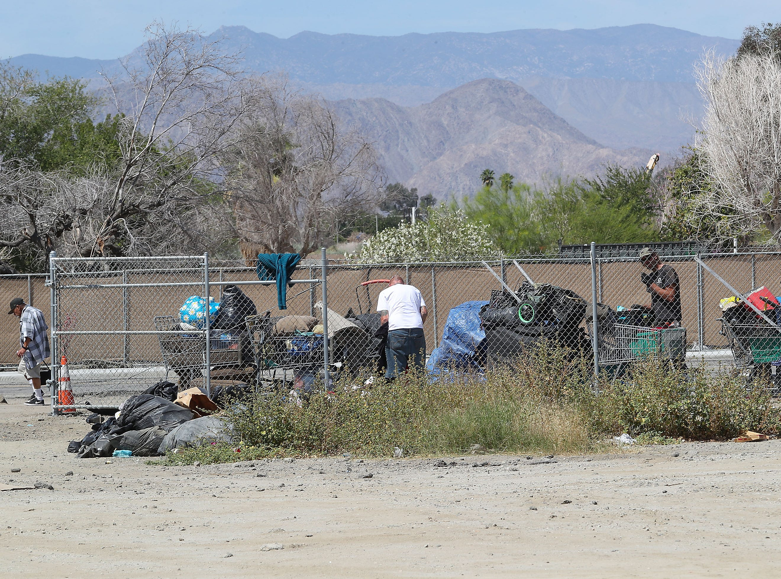 People experiencing homelessness prepare to move their camps and belongings off of a large vacant lot near the intersection of Highway 111 and Van Buren St. in Indio, April 9, 2019.
