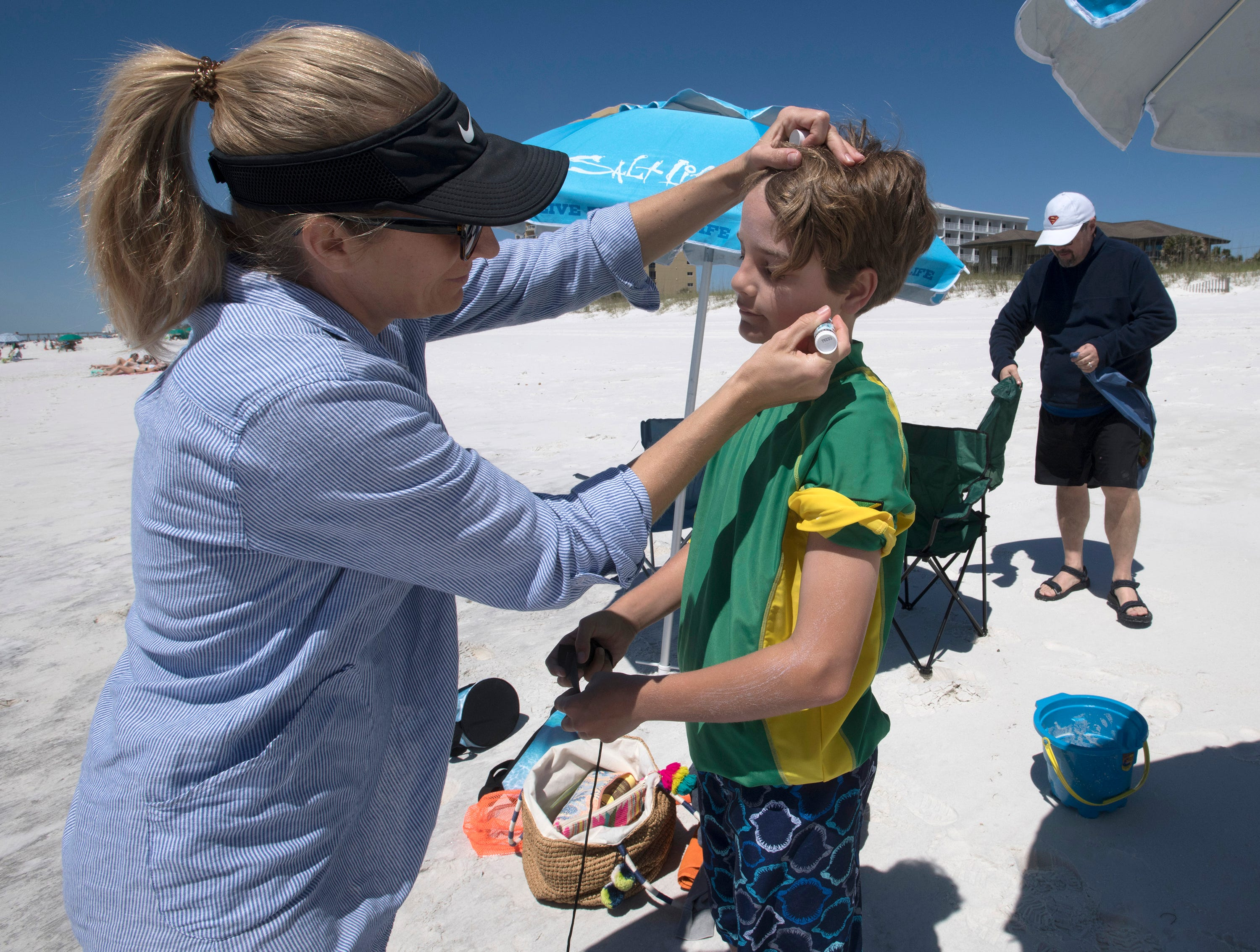 New Orleans resident, Mimi Ryan, protects her son, James, from the suns rays while visiting Pensacola Beach for spring break on Monday, April 15, 2019.