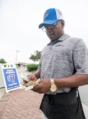 AMI Kids Pensacola behavior modification specialist Bryan Curry counts parking fees collected at Blue Wahoos Stadium before a baseball game in downtown Pensacola on Friday, April 12, 2019.  As a part of the Blue Wahoos and the Maritime Park management team's initiative to invest in community, the park extends an opportunity for local non-profit organizations to raise funds by providing volunteers to direct parking for fans at the stadium for one of the Blue Wahoos home stands each season. The non-profit organization keeps ten per cent of what they raise plus all commissions and tips.""