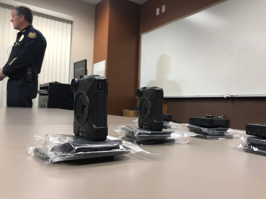 The Axon Body 2 Cameras on display with Phoenix Police Department Executive Assistant Chief Michael Kurtenbach speaking with media in the background.
