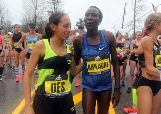 Desiree Linden, left, last year's Boston Marathon winner, embraces Edna Kiplagat, right, of Kenya, prior to the start the123rd Boston Marathon on Monday, April 15, 2019, in Hopkinton, Mass. (AP Photo/Stew Milne)