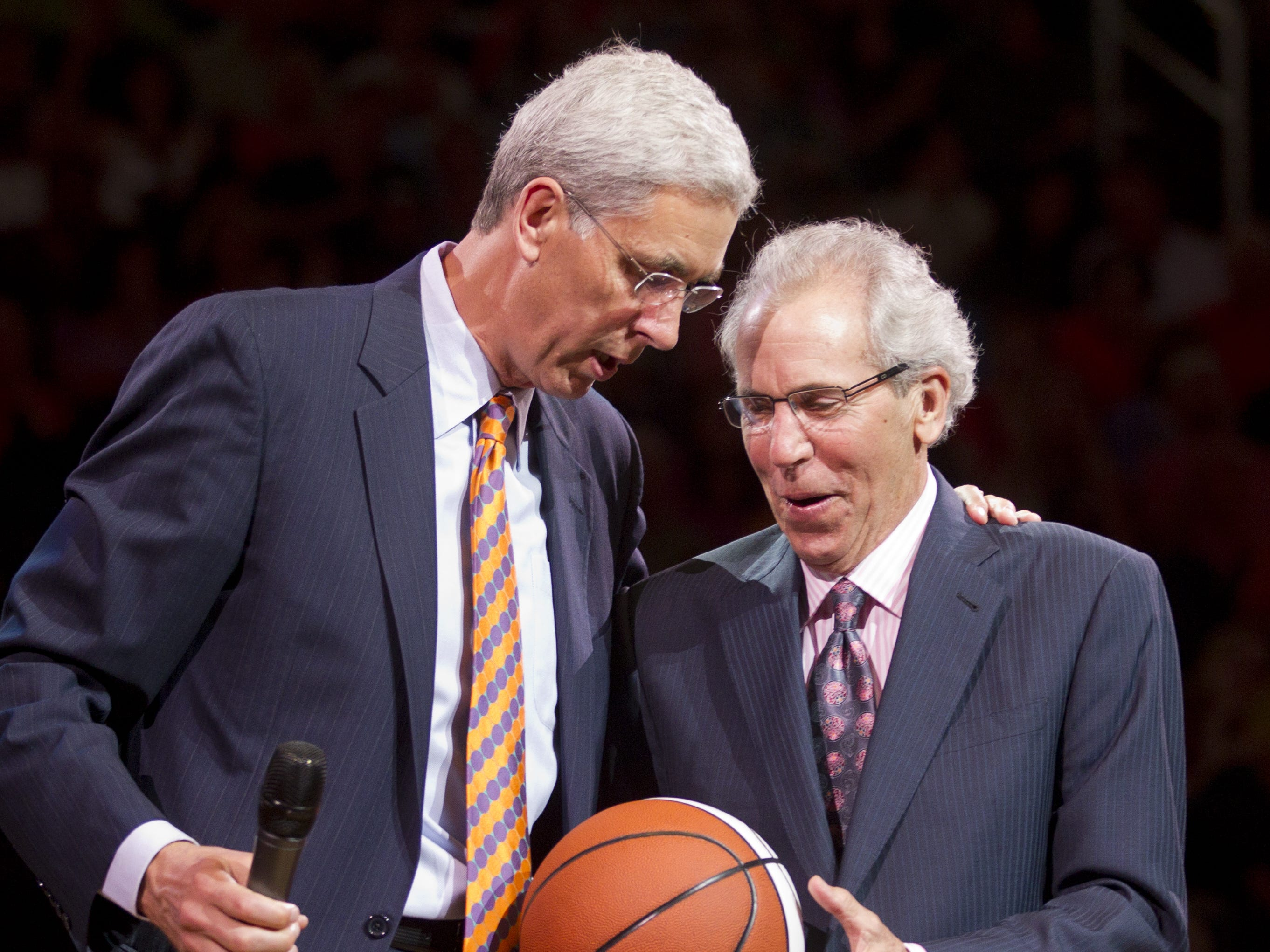 Former Suns head coach John MacLeod (right) is presented a gift by former player Alvin Adams during halftime induction ceremonies to the team's Ring of Honor in 2012.