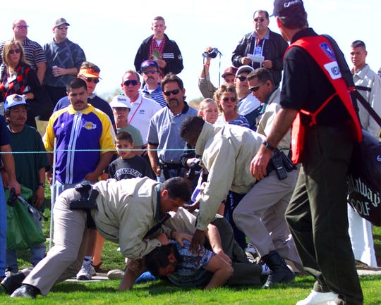 Rocco Mediate's caddie (right) watches as Scottsdale Police officers tackle a man that was carrying a gun at the 6th tee box during 4th round action in the Phoenix Open at the TPC Scottsdale in 1999.