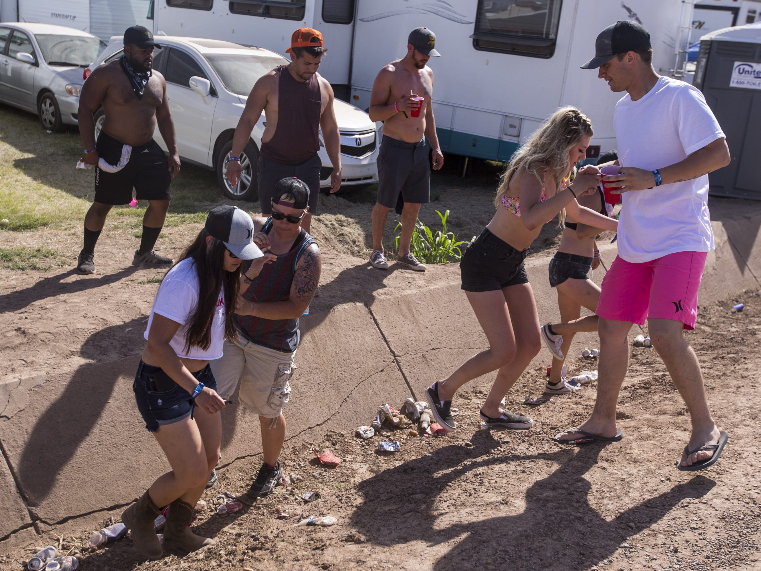 Festival-goers cross a drainage ditch on Sunday, April 14, 2019, during Day 4 of Country Thunder Arizona in Florence, Ariz.