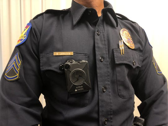 An officer shows what the new Axon Body 2 cameras look like when worn.