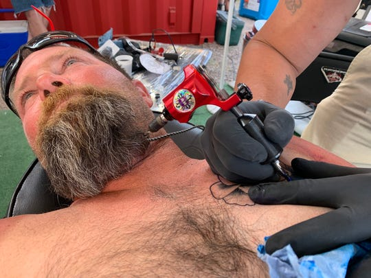 Craig MacDonald gets a tattoo of a flower on his chest at Country Thunder's first tattoo tent.