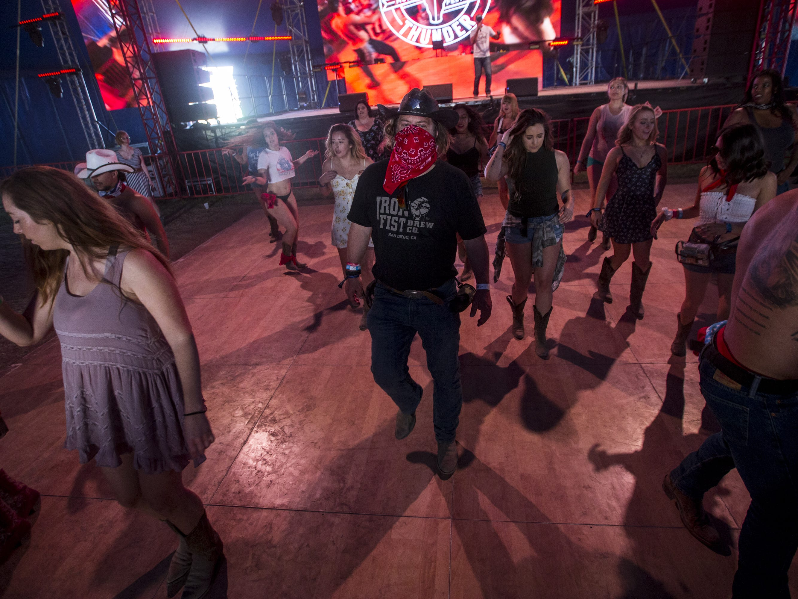 Festival-goers dance on Sunday, April 14, 2019, during Day 4 of Country Thunder Arizona in Florence, Ariz.