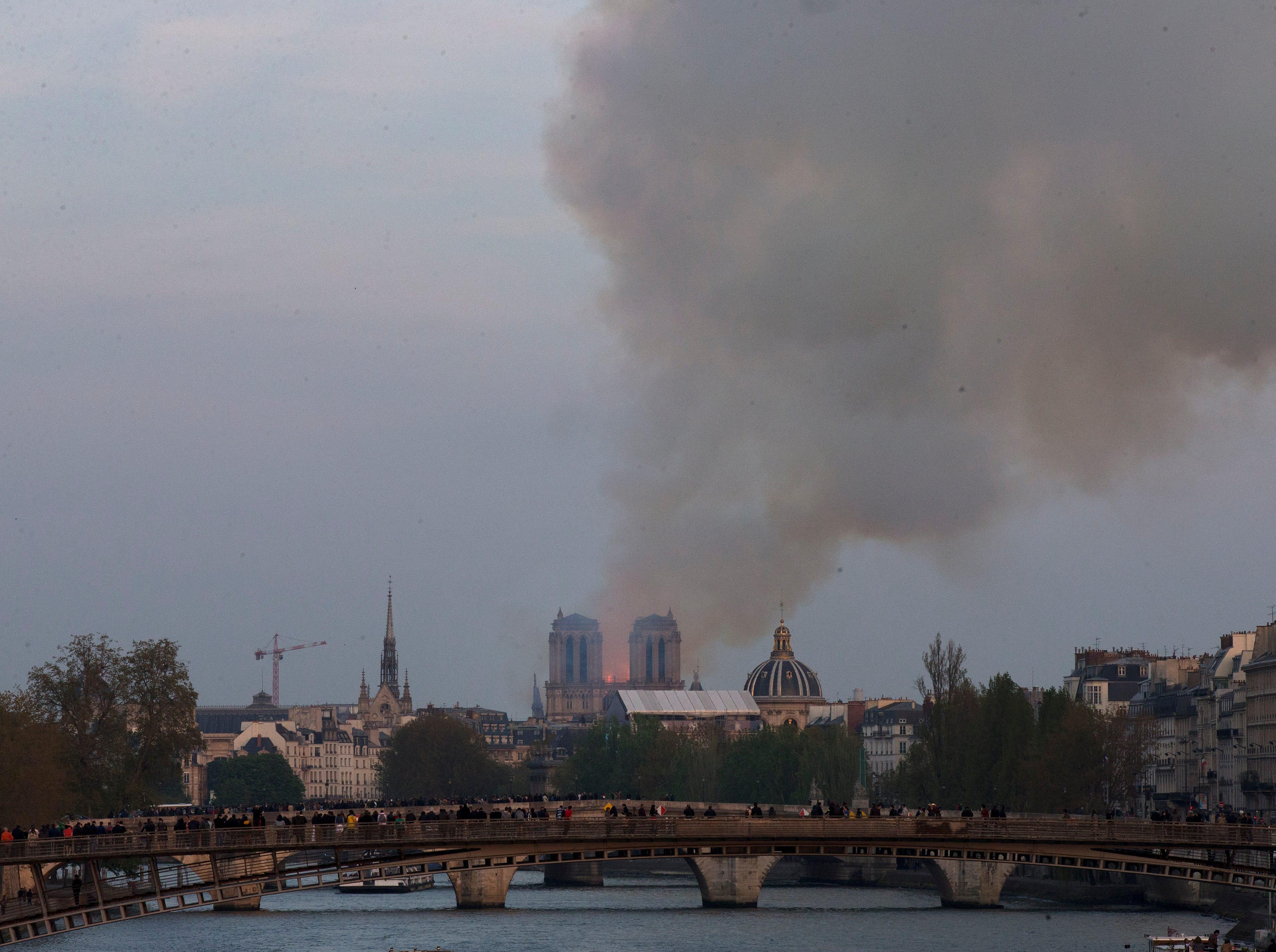 La catedral de Notre Dame se está quemando en París, el lunes 15 de abril de 2019. Grandes columnas de humo marrón amarillento llenan el aire sobre la catedral de Notre Dame y la ceniza cae sobre los turistas y otras personas alrededor de la isla que marca el centro de París.