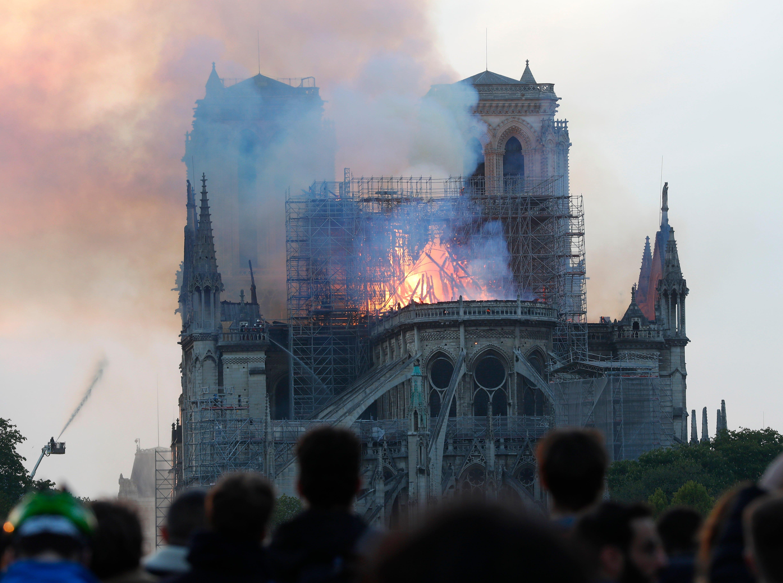 La gente observa cómo las llamas y el humo se elevan desde la catedral de Notre Dame mientras se quema en París, el lunes 15 de abril de 2019. Masas de humo marrón amarillento llenan el aire sobre la catedral de Notre Dame y la ceniza cae sobre los turistas y otros alrededor de la isla marca el centro de Paris.