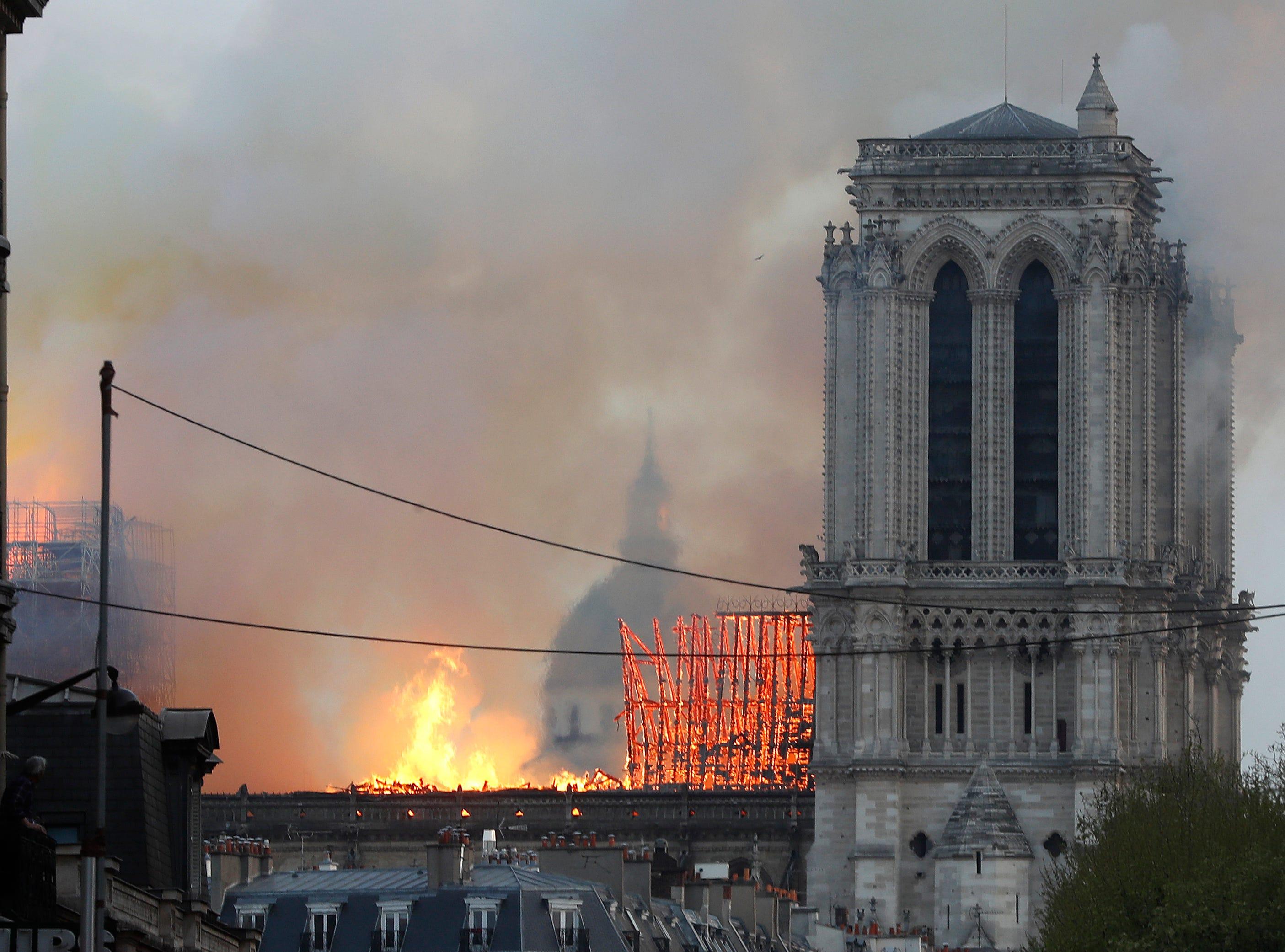 Llamas y columnas de humo se elevan desde la catedral de Notre Dame en París a medida que se quema, el lunes 15 de abril de 2019. Masas de humo marrón amarillento llenan el aire sobre la catedral de Notre Dame y caen cenizas sobre los turistas y otras personas alrededor de la isla. el centro de paris