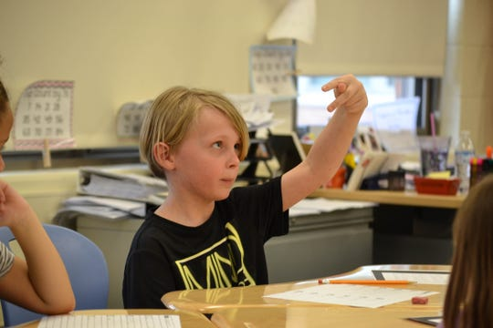 Logan Woost studies his finger placement as he forms a letter in sign. The students' sign language classes with speech therapist Jen Nickel allow them to tackle learning with a multisensory approach that uses, among other things, the brain, the eyes, and small motor skills.