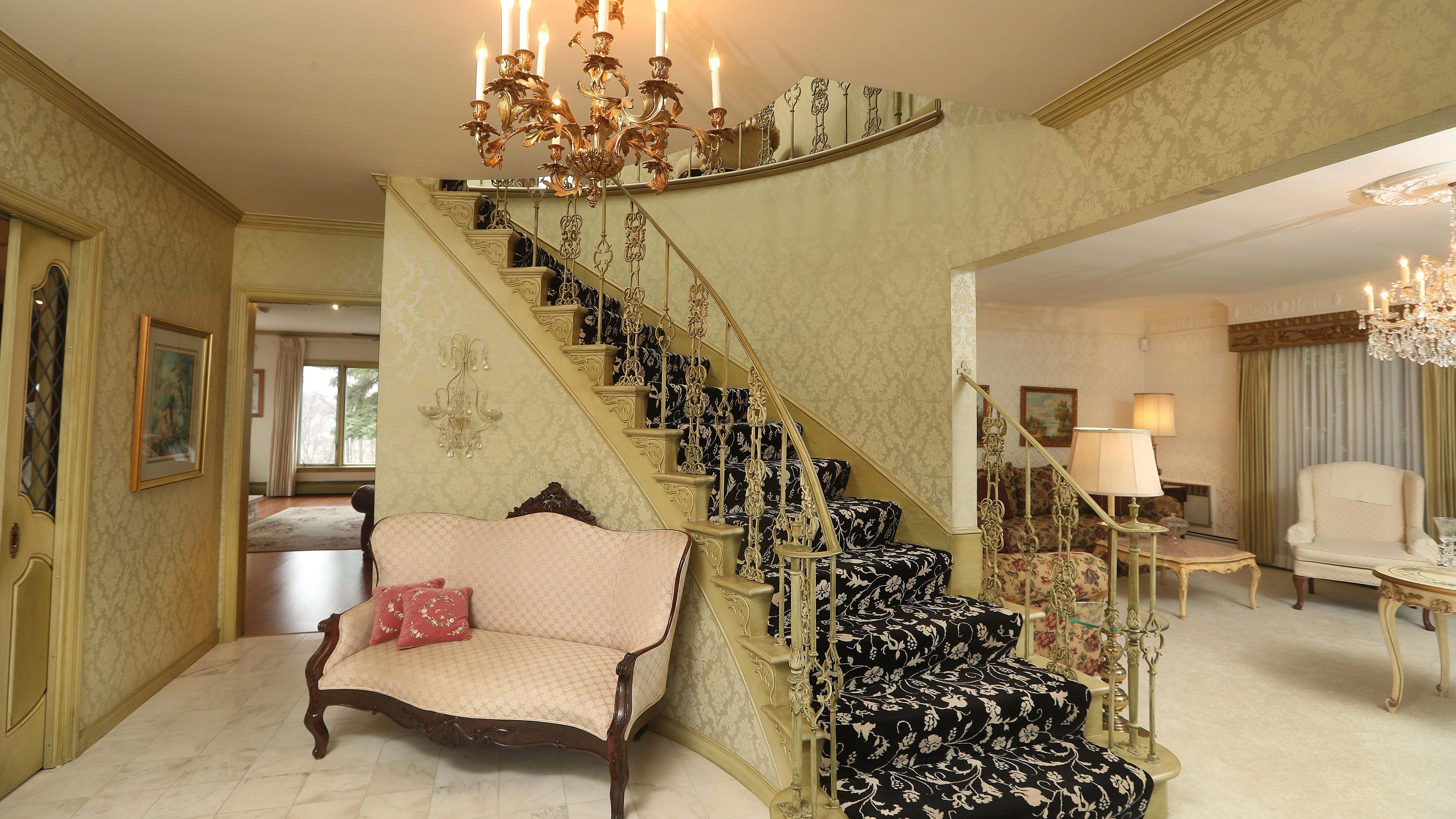A grand staircase in an open front foyer.