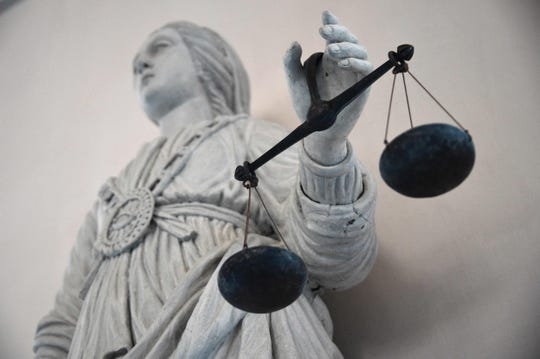 This photo shows a statue of the goddess of Justice balancing the scales.