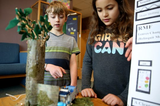 Fourth graders Micah Robinson, left, and Avalee Turner, explain their project that won the ExploraVision Science and Technology regional competition with two other students using shape-shifting leaves to reduce noise pollution. Photographed at Lee Elementary in Salem on April 15, 2019.
