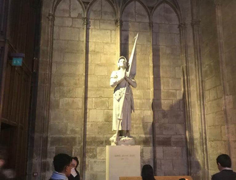 Tourists inside the Notre Dame cathedral a statue, April 8, 2019.