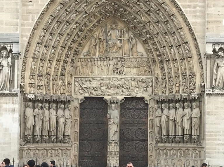 People gaze at the doors of the Notre Dame cathedral.