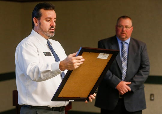 Chris Davis, left, vice president of prevention and youth support at the Community Partnership of the Ozarks, reads a proclamation before presenting it to Don Wells, right, during the Underage Drinking Task Force 20-Year Recognition Event at the Library Center on Monday, April 15, 2019.