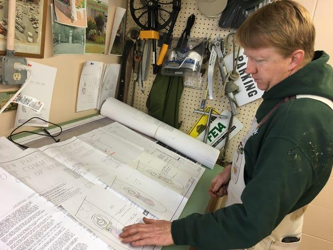 Horticulturist Matthew Sensabaugh reviews his summer flower bed plans for the watering can sculpture garden on Greenville Avenue.