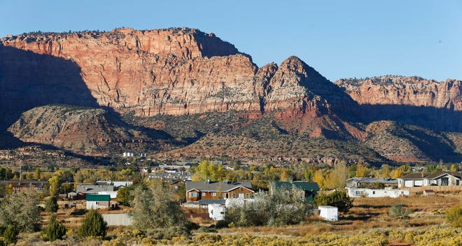 FILE - This Oct. 26, 2017, file photo, shows Hildale, Utah, sitting at the base of Red Rock Cliff mountains, with its sister city, Colorado City, Ariz., in the foreground. An Arizona county has approved an investigation to determine if voter fraud occurred during last year's election where a polygamous sect kept control of a town council in a community on the Arizona-Utah border. The Mohave County Board of Supervisors voted unanimously Monday, April 15, 2019, to allow an investigator to look into allegations that people voted using addresses where they no longer live in Colorado City. (AP Photo/Rick Bowmer, File)