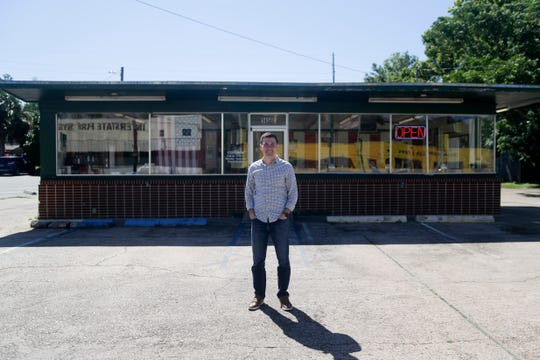 Dog Et Al Owner Operator Alex Douglas stands in front of the 35-year-old hot dog shop he recently took over Monday, April 15, 2019.