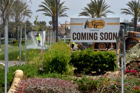 A worker erects a fence around the construction site of a Cracker Barrel restaurant at the Camarillo Premium Outlets on Monday.